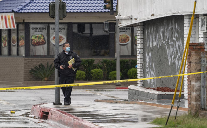 El Monte Police Chief David Reynoso, left, takes pictures of graffiti on the side wall of the First Works Baptist Church, after an explosion in El Monte, Calif., Saturday, Jan. 23, 2021. The FBI and local police are investigating an explosion early Saturday at the Los Angeles-area church that had been the target of protests for its anti-LGTBQ message. (AP Photo/Damian Dovarganes)