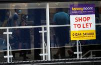 FILE PHOTO: Shoppers are reflected in the window of a closed shop following the outbreak of the coronavirus disease (COVID-19) in Chester, Britain