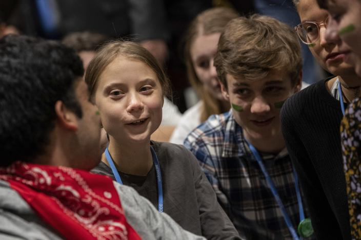 Climate activist Greta Thunberg, second left, talks with other climate activists youth at the COP25 climate talks summit in Madrid, Friday Dec. 6, 2019. Thunberg arrived in Madrid Friday to join thousands of other young people in a march to demand world leaders take real action against climate change. (AP Photo/Bernat Armangue)