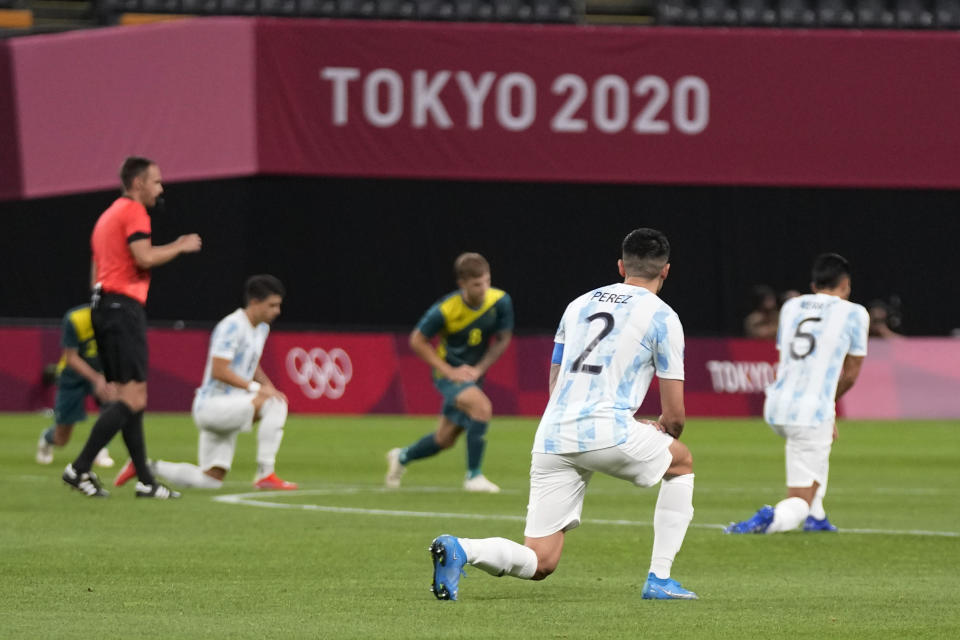 Players of Argentina and Australia kneel prior to their men's soccer match at the 2020 Summer Olympics, Thursday, July 22, 2021, in Sapporo, Japan. (AP Photo/SIlvia Izquierdo)