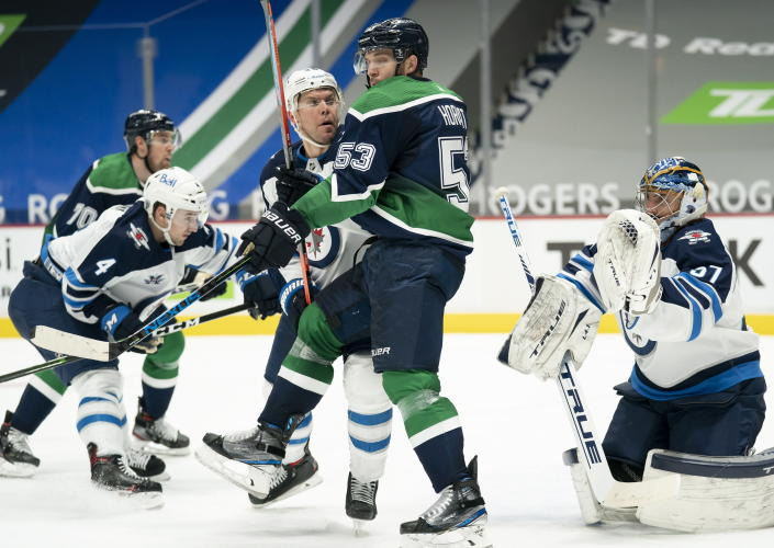 Vancouver Canucks center Bo Horvat (53) tries to screen in front of Winnipeg Jets goaltender Connor Hellebuyck (37) during the second period of an NHL hockey game Sunday, Feb. 21, 2021, in Vancouver, British Columbia. (Jonathan Hayward/The Canadian Press via AP)