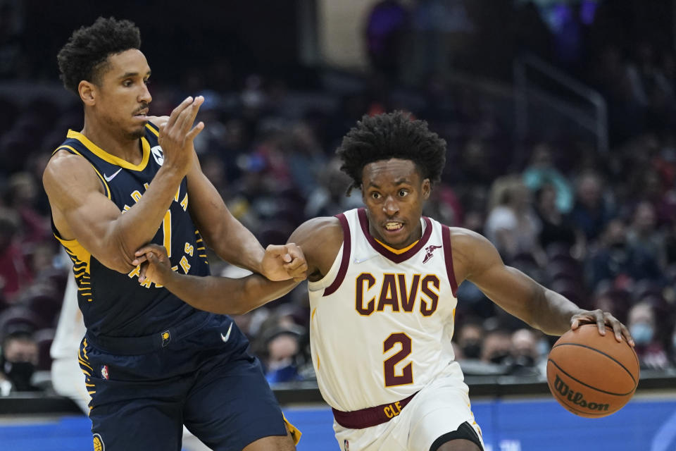 Cleveland Cavaliers' Collin Sexton (2) drives past Indiana Pacers' Malcolm Brogdon (7) in the first half of an NBA basketball preseason game, Friday, Oct. 8, 2021, in Cleveland. (AP Photo/Tony Dejak)