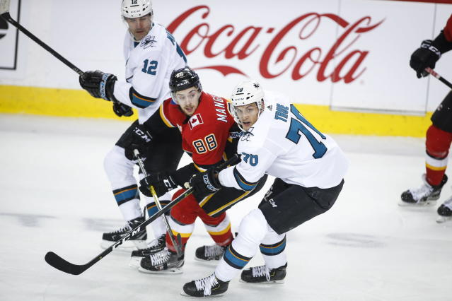 San Jose Sharks' Alex True, right, and Patrick Marleau, left, check Calgary Flames' Andrew Mangiapane during the second period of an NHL hockey game, Tuesday, Feb. 4, 2020 in Calgary, Alberta. (Jeff McIntosh/The Canadian Press via AP)