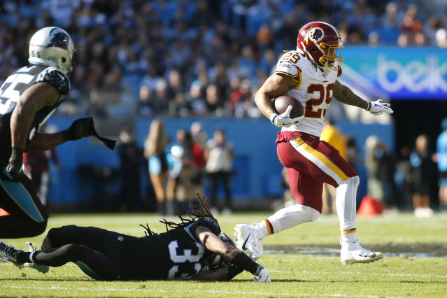 Washington Redskins running back Derrius Guice (29) runs the ball while Carolina Panthers free safety Tre Boston (33) dives to tackle during the first half of an NFL football game in Charlotte, N.C., Sunday, Dec. 1, 2019. (AP Photo/Brian Blanco)