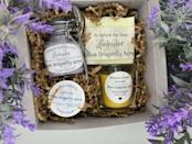 """<p><strong>Blue Dragonfly Acres</strong></p><p>etsy.com</p><p><strong>$26.99</strong></p><p><a href=""""https://go.redirectingat.com?id=74968X1596630&url=https%3A%2F%2Fwww.etsy.com%2Flisting%2F738380716%2Flavender-gift-box-birthday-lavender-gift&sref=https%3A%2F%2Fwww.goodhousekeeping.com%2Fholidays%2Fgift-ideas%2Fg34054234%2Fbest-gift-baskets-for-women%2F"""" rel=""""nofollow noopener"""" target=""""_blank"""" data-ylk=""""slk:Shop Now"""" class=""""link rapid-noclick-resp"""">Shop Now</a></p><p>If there's one scent that instantly puts you at ease, it's lavender. This gift box comes with a scented candle, body butter, bar soap, and body scrub, all boasting the calming fragrance. </p>"""