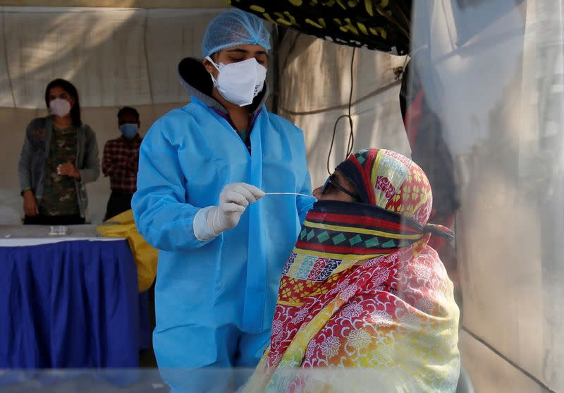 A healthcare worker collects a swab sample from a woman during a rapid antigen testing campaign for the coronavirus disease (COVID-19), in Ahmedabad