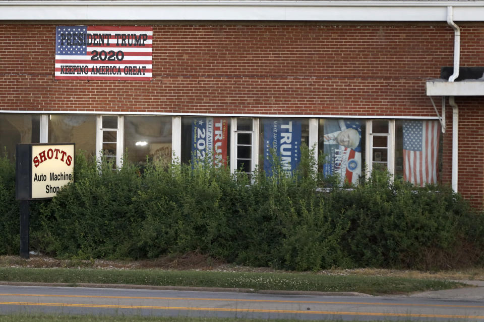 Banners in support of former President Donald Trump still hang in the windows of the Shotts Auto Machine Shop Monday, June 14, 2021, in Galesburg, Ill. Like so many places, Galesburg, a city of about 30,000 people in western Illinois, is starting to emerge from the fog of the COVID-19 pandemic, and to address longs-festering conflicts from the Trump era. (AP Photo/Shafkat Anowar)