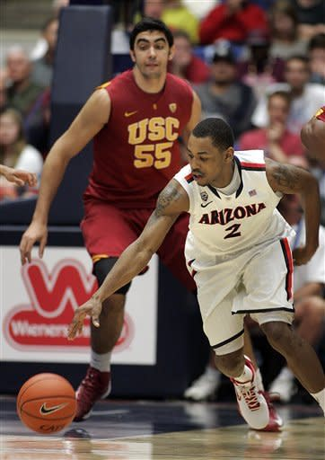 Arizona's Mark Lyons (2) struggles with the ball in front of Southern California's Omar Oraby (55) during the second half of an NCAA basketball game at McKale Center in Tucson, Ariz., Saturday, Jan. 26, 2013. (AP Photo/John Miller)