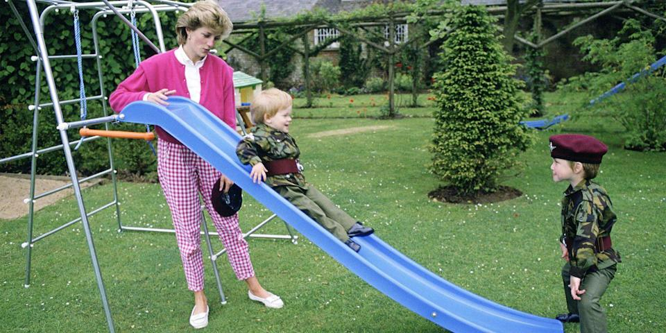 <p>Pushing Prince Harry down the slide as both Princes are dressed up in miniature parachute regiment uniforms.</p>