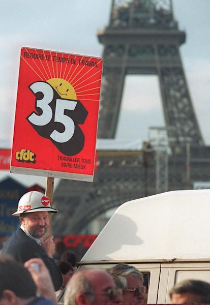 "A picture taken on October 15, 1993 shows a protester holding a placard reading ""35 hours: reduce working hours"" during a demonstration in Paris (AFP Photo/Eric Feferberg)"