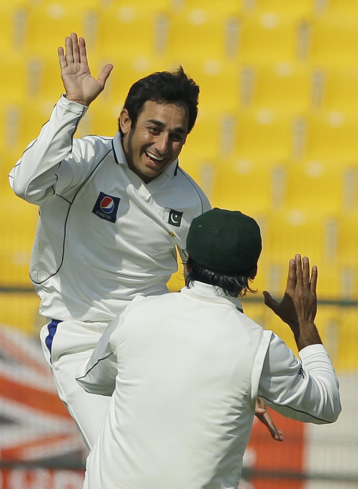 Pakistan's Saeed Ajmal, left, leaps in the air as he celebrates with his teammate Mohammad Hafeez, right, after taking the wicket of England's Ian Bell during the fourth day of the second cricket test match of a three match series between England and Pakistan at Zayed Cricket Stadium in Abu Dhabi, United Arab Emirates, Saturday, Jan. 28, 2012. (AP Photo/Hassan Ammar)