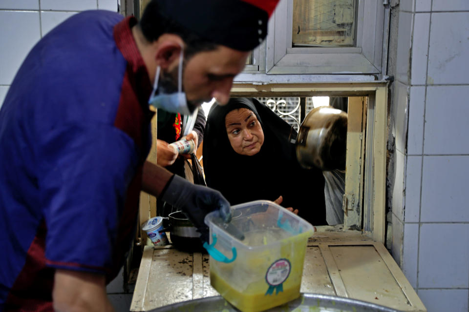 People receive free food being distributed ahead of Iftar, the evening meal breaking the Ramadan fast, at the Abdul-Qadir al-Gailani mosque in Baghdad, Iraq, Tuesday, May 11, 2021. Muslims throughout the world are marking the last days of Ramadan -- a month of fasting during which observants abstain from food, drink and other pleasures from sunrise to sunset. (AP Photo/Khalid Mohammed)