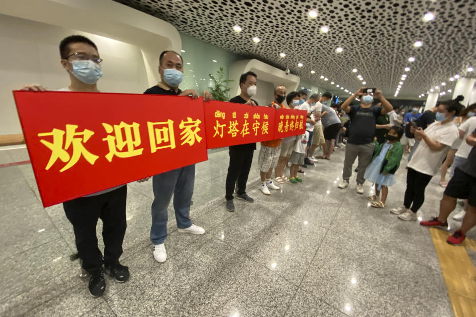"""Supporters of Huawei CFO Meng Wanzhou hold a banner reading: """"Welcome Home"""" at Shenzhen Bao'an International Airport in Shenzhen in southern China's Guangdong Province, Saturday, Sept. 25, 2021. China's government was eagerly anticipating the return of a top executive from global communications giant Huawei Technologies on Saturday following what amounted to a high-stakes prisoner swap with Canada and the U.S. (AP Photo/Ng Han Guan)"""