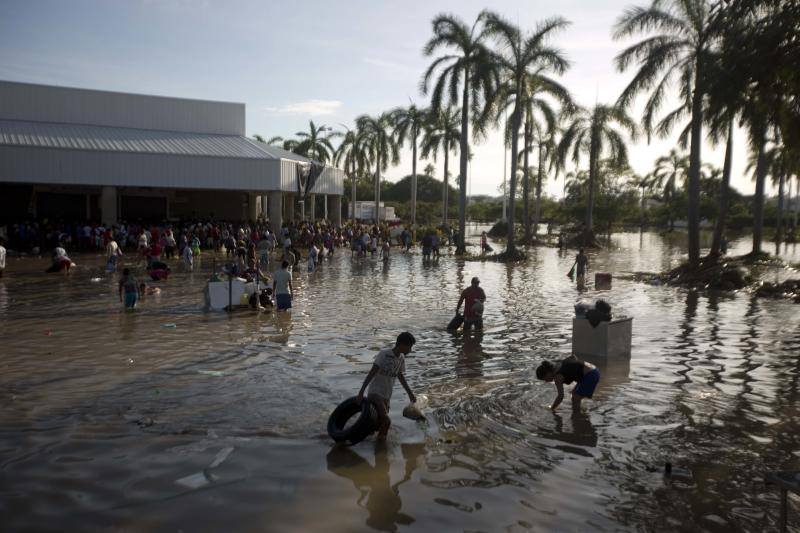 People wade through waist-high water in a store's parking, looking for valuables, south of Acapulco, in Punta Diamante, Mexico, Wednesday, Sept. 18, 2013. Mexico was hit by the one-two punch of twin storms over the weekend, and the storm that soaked Acapulco on Sunday - Manuel -re-formed into a tropical storm Wednesday, threatening to bring more flooding to the country's northern coast. With roads blocked by landslides, rockslides, floods and collapsed bridges, Acapulco was cut off from road transport. (AP Photo/Eduardo Verdugo)