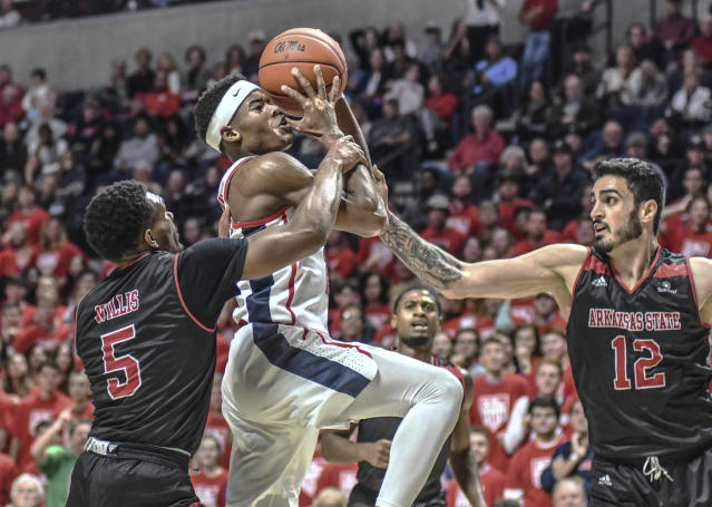 Mississippi's Devontae Shuler (2) is fouled by Arkansas State's Christian Willis (5) as Arkansas State's Canberk Kus (12) also defends during the first half of an NCAA college basketball game, Friday, Nov. 8, 2019 in Oxford, Miss. (Bruce Newman/The Oxford Eagle via AP)