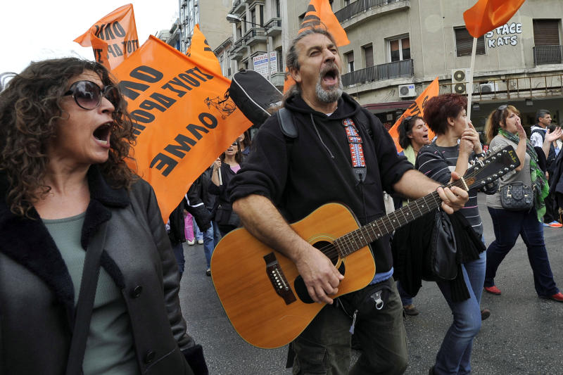 A teacher plays guitar as his colleagues shout slogans during a rally in the northern Greek port city of Thessaloniki, Wednesday, Nov. 6, 2013. Services across Greece shut down Wednesday as unions held a 24-hour general strike to protest further austerity cuts in the cash-strapped country. (AP Photo/Nikolas Giakoumidis)
