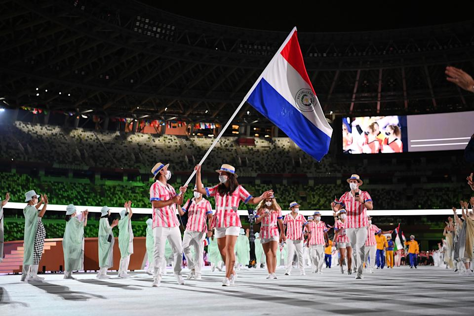<p>TOKYO, JAPAN - JULY 23: Flag bearers Veronica Cepede Royg and Fabrizio Zanotti of Team Paraguay during the Opening Ceremony of the Tokyo 2020 Olympic Games at Olympic Stadium on July 23, 2021 in Tokyo, Japan. (Photo by Matthias Hangst/Getty Images)</p>