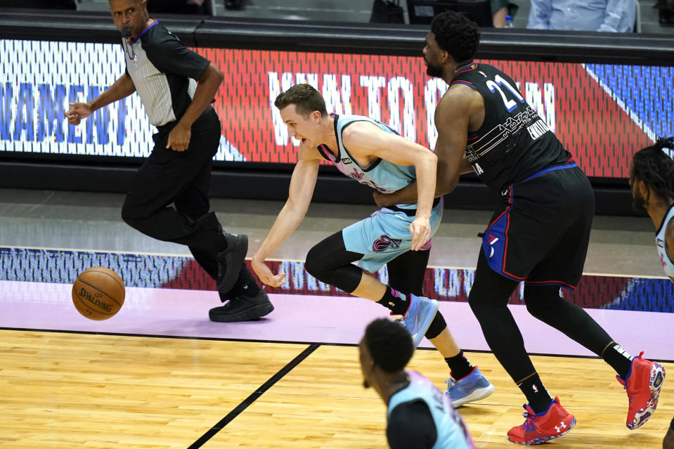 Miami Heat guard Duncan Robinson, left is fouled by Philadelphia 76ers center Joel Embiid (21) during the first half of an NBA basketball game Thursday, May 13, 2021, in Miami. (AP Photo/Lynne Sladky)