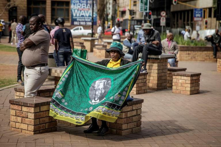 A woman holds a cloth bearing the portrait of late South African president Nelson Mandela as South African ruling party African National Congress disgruntled members demonstrate near by the ANC headquarter demanding the resignation of South African president Jacob Zuma and the National Executive Commitee on September 5, 2016 in Johannesburg, South Africa.Activists from rival factions of South Africa's Africa National Congress (ANC) faced off in central Johannesburg on September 5, highlighting deep divisions in the ruling party as pressure grows on President Jacob Zuma. The ANC, which led the struggle to end apartheid, has been rocked by poor recent local election results largely blamed on Zuma's leadership and the country's mounting economic woes. Police patrolled outside the ANC's Luthuli House headquarters in central Johannesburg after some party activists vowed to occupy the building in protest at how the party and the government are being run. As about 40 anti-Zuma protesters gathered nearby, other ANC members loyal to the president pledged to defend the building