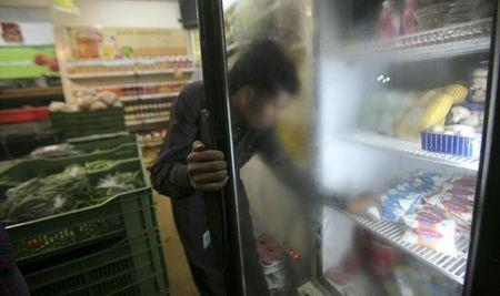 A man takes out a packet of yogurt from a refrigerator at a food store in Noida