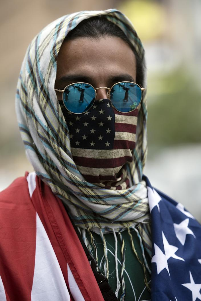 """An American flag mask such as the one worn by Jayse Garcia at a recent demonstration in Hollywood might sway a patriotic but otherwise mask-averse man to wear one. <span class=""""copyright"""">(Francine Orr / Los Angeles Times)</span>"""