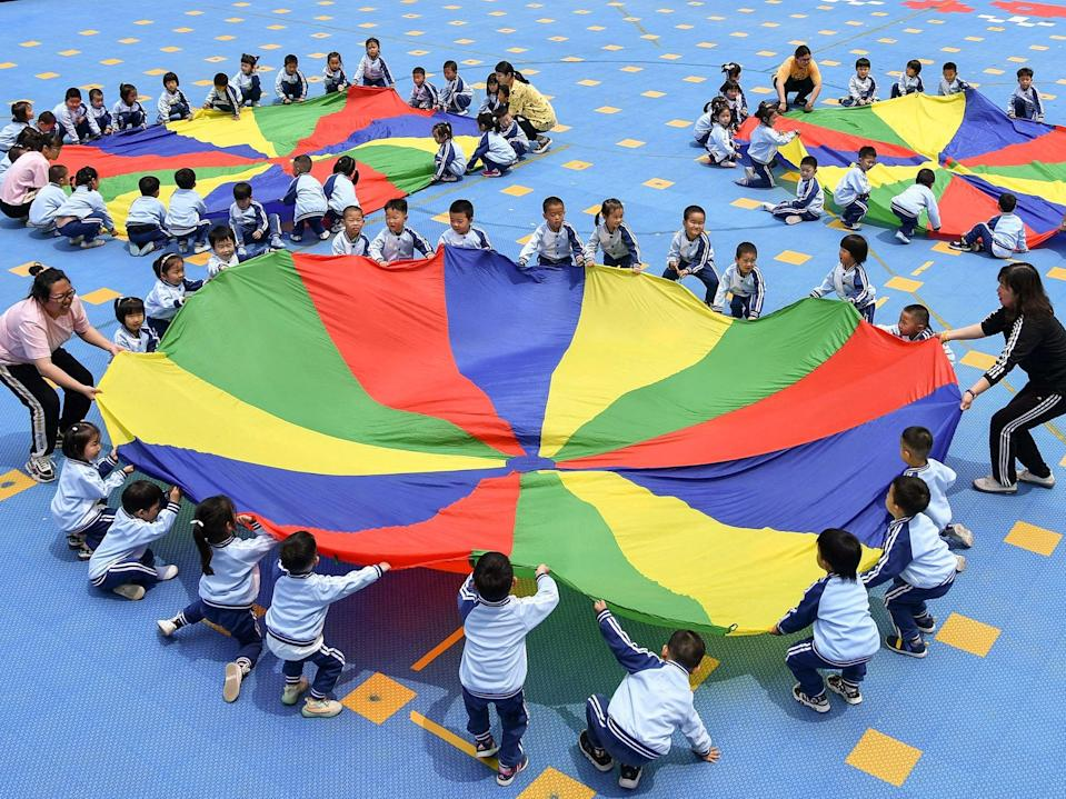 <p>Children play at a kindergarten in Yantai, Shandong, on 31 May 2021</p> (AFP/Getty)
