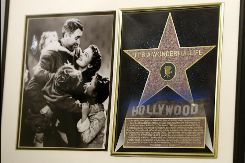 """In this photo made on Friday, Dec. 20, 2013, a framed plaque with a photograph of a scene from the 1946 film """"It's A Wonderful Life"""" starring Jimmy Stewart, left, and a Hollywood star are on display at the Jimmy Stewart Museum in Indiana, Pa. The museum dedicated to the life of the star of many films including the holiday favorite """"It's A Wonderful Life"""" is located in the off-the-beaten track town where Stewart grew up. The museum still attracts visitors from all over the country. It's full of displays not just about Hollywood, but about Stewart's service as a bomber pilot in World War II, his well-to-do ancestors, and his family life. (AP Photo/Keith Srakocic)"""