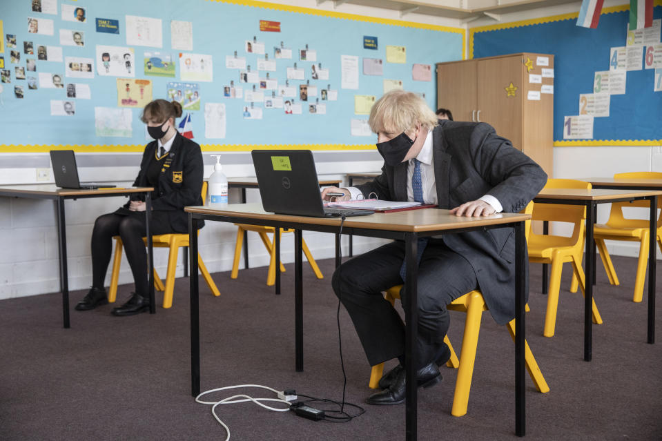 <p>Britain's Prime Minister Boris Johnson takes part in an online class, during a visit to Sedgehill School in Lewisham, south east London, Tuesday, Feb. 23, 2021, to see preparations for students returning to school. Johnson has announced a gradual easing of one of Europe's strictest lockdowns on, saying children will return to class and people will be able to meet a friend for coffee in a park in two weeks' time. But people longing for a haircut, a restaurant meal or a pint in a pub have almost two months to wait, and people won't be able to hug loved ones that they don't live with until May at the earliest. (Jack Hill/Pool Photo via AP)</p>