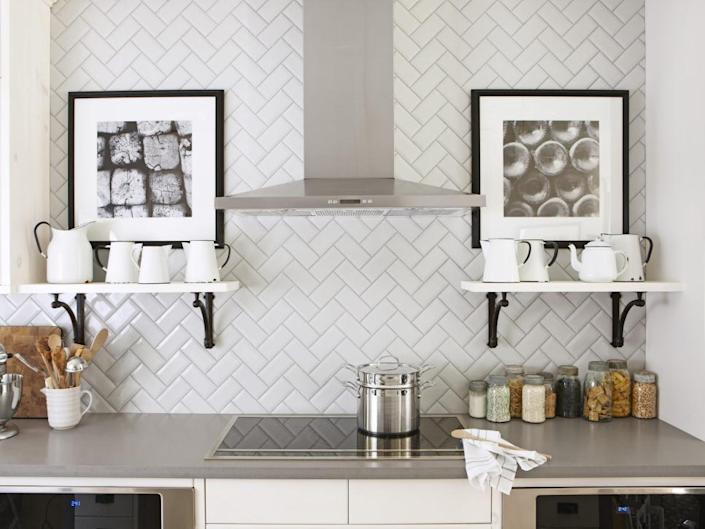 """<p>One of the easiest ways to mix up your kitchen's backsplash design is by laying tile in a fun, unexpected pattern, such as this herringbone design featured in <i><a href=""""http://www.hgtv.com/design/packages/hgtv-magazine?oc=PTNR-YahooRealEstate-HGTV-subway_tile_twists"""" rel=""""nofollow noopener"""" target=""""_blank"""" data-ylk=""""slk:HGTV Magazine"""" class=""""link rapid-noclick-resp"""">HGTV Magazine</a></i>. By pairing the design with simple shelves and black-and-white art, the charming tilework remains the star of the space. <i>Photo by Stacey Brandford. </i></p>"""