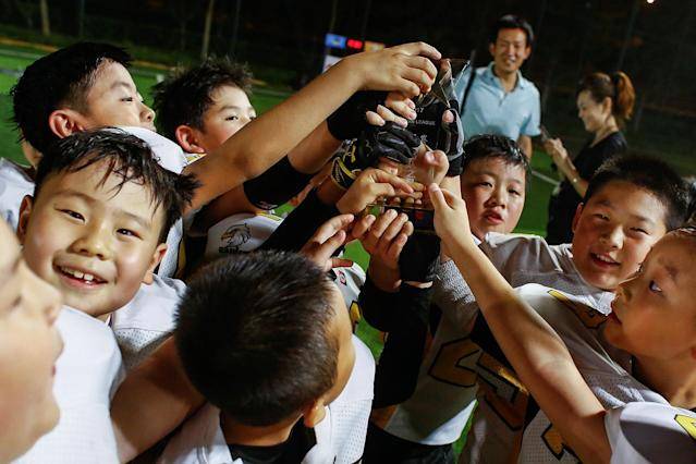<p>Eagles players celebrate after they defeated the Sharklets in a Future League American football youth league match in Beijing, May 26, 2017. (Photo: Thomas Peter/Reuters) </p>