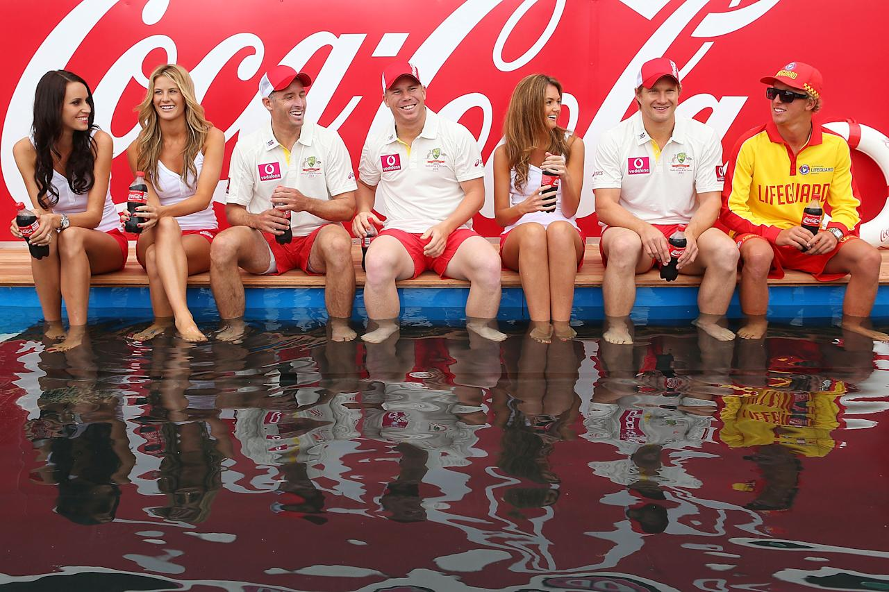 "SYDNEY, AUSTRALIA - JANUARY 02:  (C) Shane Watson, David Warner and Michael Hussey of Australia pose with models during a ""COCA-COLA Beach at the Cricket"" event at Sydney Cricket Ground on January 2, 2013 in Sydney, Australia.  (Photo by Brendon Thorne/Getty Images)"