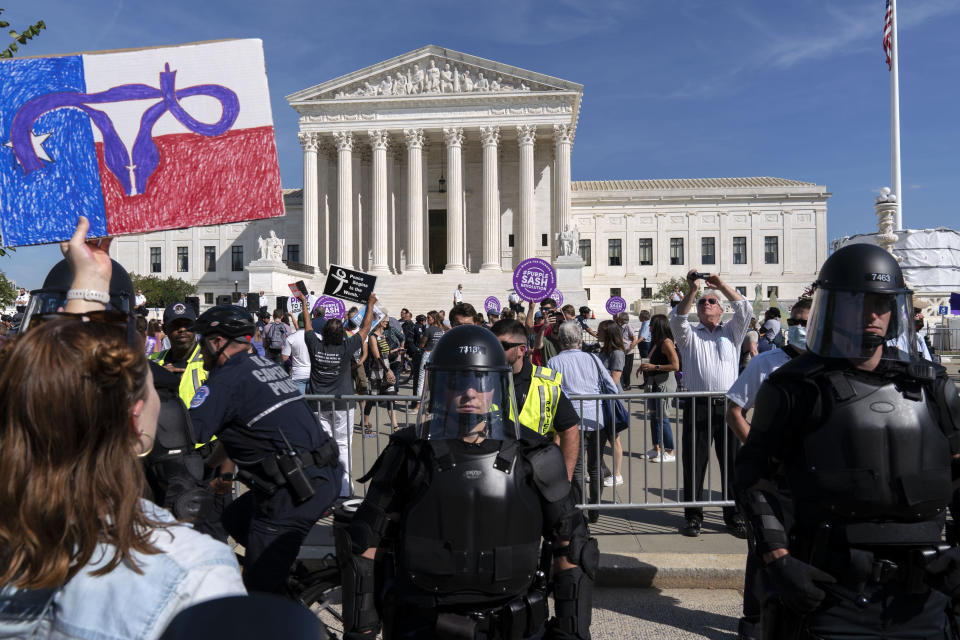 Demonstrators march outside of the the U.S. Supreme Court as police officers in riot gear looks on, during the Women's March in Washington, Saturday, Oct. 2, 2021. (AP Photo/Jose Luis Magana)