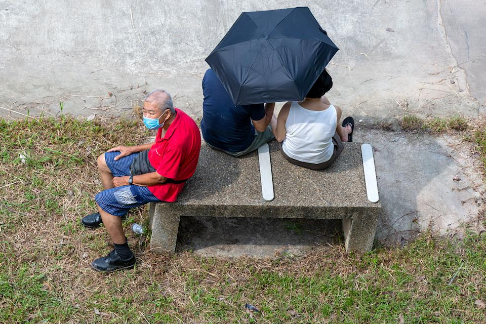 An elderly man in a face mask shares a bench with a couple. (PHOTO: Dhany Osman / Yahoo News Singapore)
