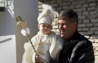 Parent holds his child as they take part in a mass circumcision ceremony in the village of Ribnovo, Bulgaria, Sunday, April 11, 2021. Despite the dangers associated with COVID-19 and government calls to avoid large gatherings, Hundreds of people flocked to the tiny village of Ribnovo in southwestern Bulgaria for a four-day festival of feasting, music and the ritual of circumcision which is considered by Muslims a religious duty and essential part of a man's identity. (AP Photo/Jordan Simeonov)