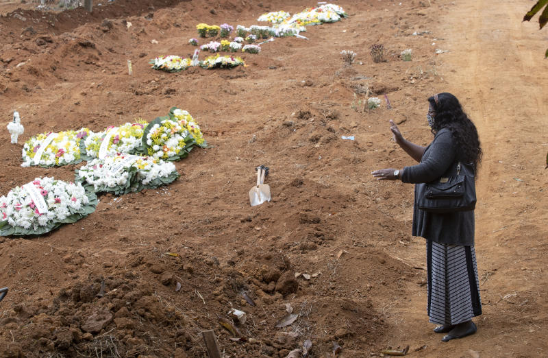 Vera Lucia Souza prays at the gravesite of her 47-year-old brother Paulo Roberto da Silva, who died of COVID-19, during his burial at the Sao Luiz cemetery in Sao Paulo, Brazil, Thursday, June 4, 2020. (AP Photo/Andre Penner)