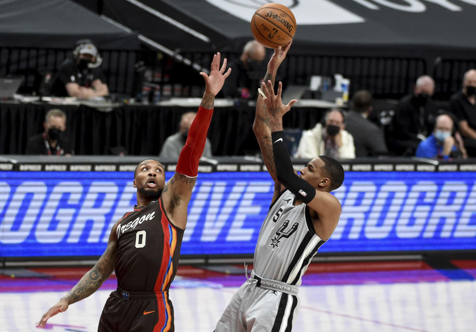San Antonio Spurs guard Dejounte Murray, right, shoots over Portland Trail Blazers guard Damian Lillard during the first half of an NBA basketball game in Portland, Ore., Saturday, May 8, 2021. (AP Photo/Steve Dykes)