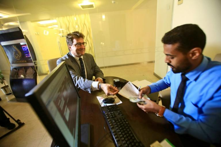 Keith Hughes, public affairs officer at the US Embassy in Khartoum, opens an account at a branch of the Bank of Khartoum (AFP Photo/ASHRAF SHAZLY)