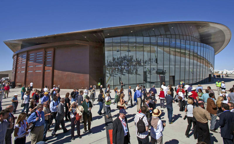 FILE - In this Oct. 17, 2011 file photo, guests stand outside the new Spaceport America hangar in Upham, N.M. Virgin Galactic is scheduled to unveil the interior of its digs at Spaceport America, providing the first glimpse of mission control, a prep area for pilots and where paying customers will lounge ahead of their suborbital flights. Company officials are gathering Thursday, Aug. 15, 2019, at the remote facility in the New Mexico desert to show off two levels of the custom-tailored hangar at the taxpayer-financed spaceport.  (AP Photo/Matt York, File)