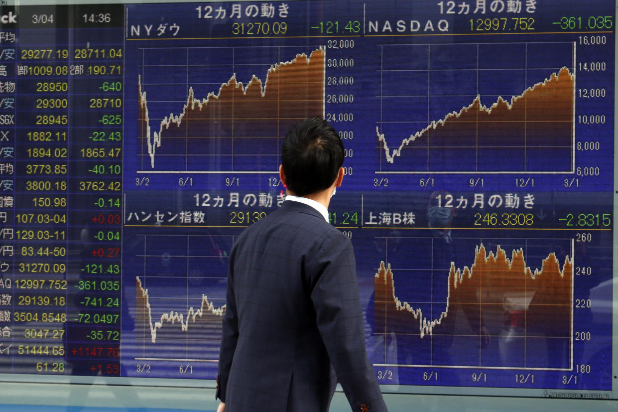 TOKYO, JAPAN - 2021/03/04: A man walks past a Nikkei stock index at a brokerage in Tokyo. Japan's equity benchmark fell 2% on Thursday as investors continued to fret over rising U.S. Treasury yields, while other Asian stock markets also retreated. (Photo by James Matsumoto/SOPA Images/LightRocket via Getty Images)