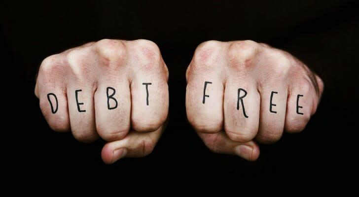 """Debt Free"" written on a man's fingers"