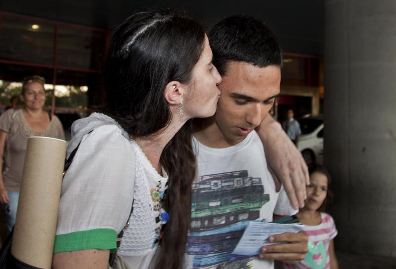 Cuban dissident blogger Yoani Sanchez kisses her son Teo Escobar upon her arrival at the Jose Marti International Airport in Havana, Cuba, Thursday, May 30, 2013. Sanchez is back home after a more than three-month globe-trotting tour that has turned her into the most internationally recognizable face in the island's small dissident community. Sanchez has been on the road since Feb. 17 and visited more than a dozen countries in Europe and the Americas. (AP Photo/Ramon Espinosa)
