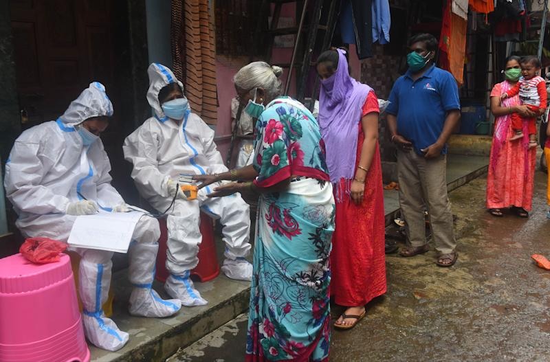 BMC Health worker and Doctor conduct thermal screening and pulse test of a resident at Dharavi during Covid 19 pandemic, on August 11, 2020 in Mumbai, India. (Photo: Hindustan Times via Getty Images)