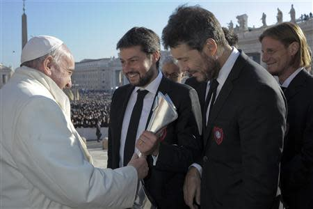 Members of Argentine soccer team San Lorenzo presents Pope Francis (L) with a replica of the Argentine soccer championship trophy during the Wednesday general audience in St Peter's Square at the Vatican December 18, 2013. REUTERS/Osservatore Romano