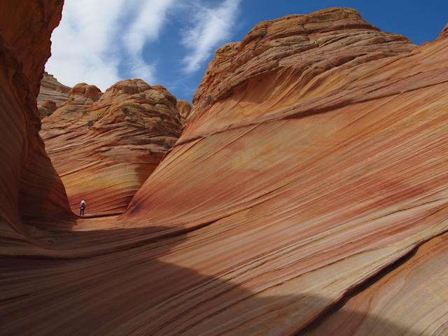 This May 28, 2013 photo shows a hiker on a rock formation known as The Wave in the Vermilion Cliffs National Monument in Arizona. The U.S. Bureau of Land Management limits the number of permits for hikers to 20 a day in order to preserve the backcountry wilderness experience and protect the sandstone formation. (AP Photo/Brian Witte)