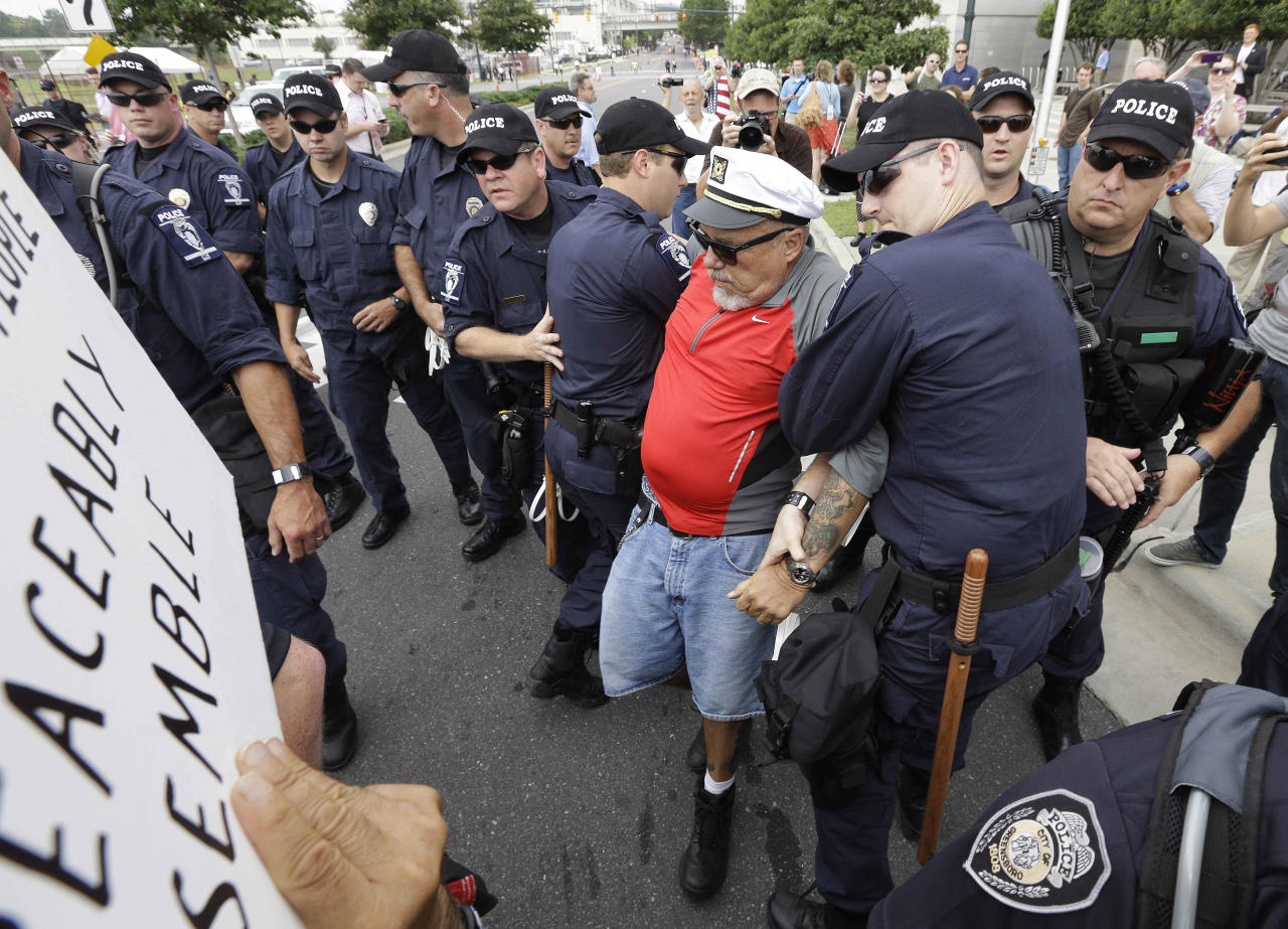 A demonstrator known only as the Captain is detained by police during an unscheduled protest march,Tuesday, Sept. 4, 2012, in Charlotte, N.C. The Democratic National Convention begins today. (AP Photo/Patrick Semansky)