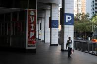 A man walks by an almost empty area of the city following the implementation of stricter social-distancing and self-isolation rules to limit the spread of the coronavirus disease (COVID-19) in Sydney