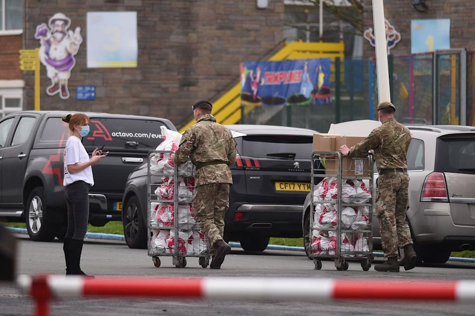"""An NHS worker speaks with soldiers as they carry supplies at Pontin's Southport Holiday Park, north of Liverpool on November 5, 2020, prior to assisting in a mass and rapid testing pilot scheme for the novel coronavirus COVID-19, in Liverpool. - Prime Minister Boris Johnson promised """"light ahead"""" for weary Britons ahead of a second coronavirus lockdown, pinning his hopes partly on the UK's first city-wide testing plan in Liverpool, one of the areas worst-hit by the pandemic. (Photo by Oli SCARFF / AFP) (Photo by OLI SCARFF/AFP via Getty Images)"""