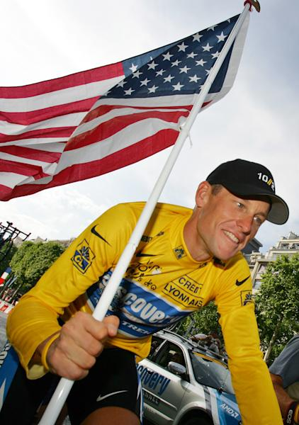 FILE - In this July 24, 2005 file photo, Lance Armstrong, of Austin, Texas, carries the United States flag and wears a jersey with Nike logos during a victory parade on the Champs Elysees avenue in Paris, after winning his seventh straight Tour de France cycling race. Armstrong stepped down as chairman of his Livestrong cancer-fighting charity and Nike severed ties with him as fallout from the doping scandal swirling around the famed cyclist escalated Wednesday, Oct. 17, 2012. (AP Photo/Peter Dejong, File)