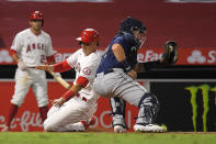 Los Angeles Angels' Jason Castro, center, scores on a double by Brian Goodwin as Seattle Mariners catcher Joseph Odom, right, takes a late throw during the sixth inning of a baseball game Wednesday, July 29, 2020, in Anaheim, Calif. (AP Photo/Mark J. Terrill)