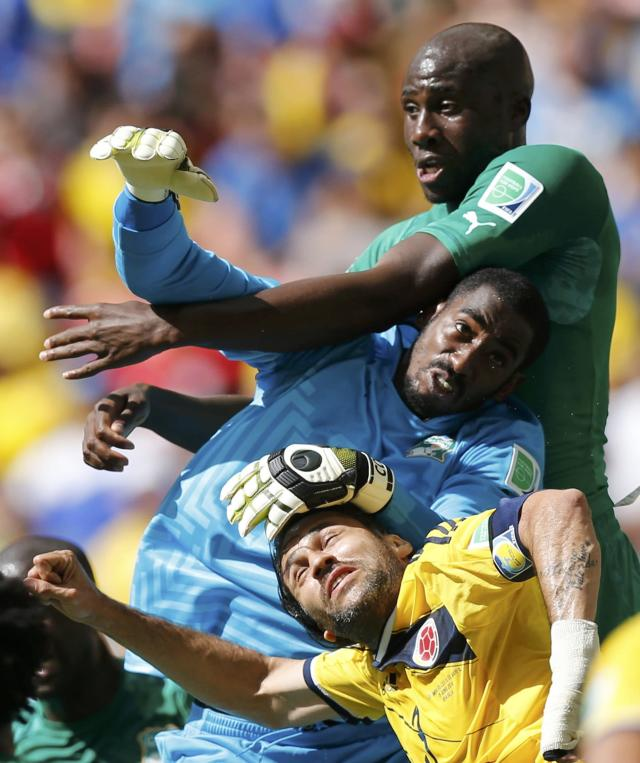 Colombia's Mario Yepes (bottom) fights for the ball with Ivory Coast's Boubacar Barry (C) and Souleyman Bamba during their 2014 World Cup Group C soccer match at the Brasilia national stadium in Brasilia June 19, 2014. REUTERS/Ueslei Marcelino (BRAZIL - Tags: SOCCER SPORT WORLD CUP)